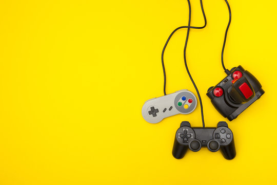 Retro computer gaming controllers on a bright yellow background