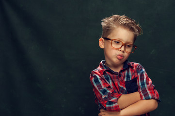 Blurred portrait of small cute boy with sad, pensive face in glasses and stylish hairdo on green background