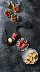Ingredients for making tapas or bruschetta. Crusty bread, ham prosciutto, sun dried tomatoes, olive oil, olives, pepper with wooden serving board over dark texture background. Top view with space