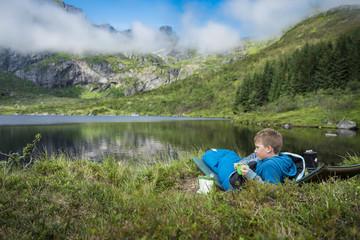 Boy relaxing by lake