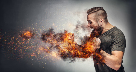 Excited man in fighting gesture with fists on fire.