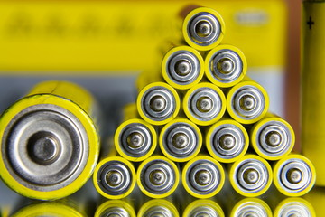 Stack of yellow AA batteries close up abstract coloured background