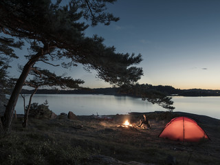 Tent and campfire by lake