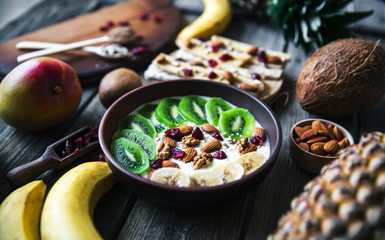 Yogurt with different fruits on a wooden background. Useful food, diet, organic.