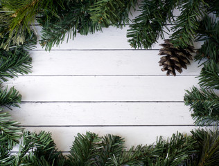 Christmas composition with fir tree and cones. White wood plank background.