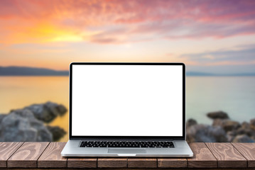 Modern laptop with empty white screen on wooden table against blurred landscape background
