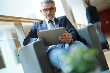 Businessman in airport waiting area connected with tablet