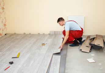 handyman laying down laminate flooring boards