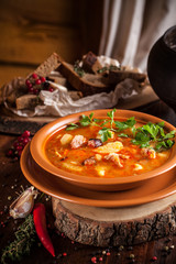 Traditional Russian and Ukrainian cuisine, lunch, first course, red soup in a clay dish on a wooden table