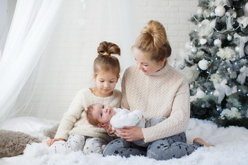 Happy woman,cheerful mother and little children,a girl and a newborn boy sitting on a fluffy white blanket beside the Christmas festive green Christmas tree with white toys,snowflakes,glowing lights