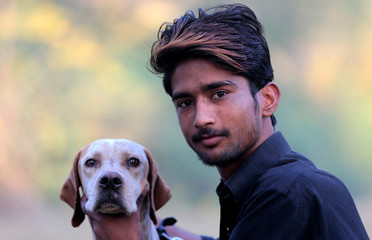 A dog walker poses for a picture with his dog in a park in Islamabad