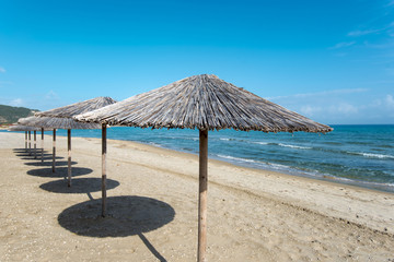 Sarty, Greece, Summer beach without people, sea and sand, empty sea and beach background with straw umbrellas