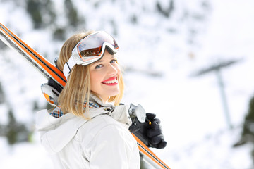 Happy skier girl ready to ski in a slope