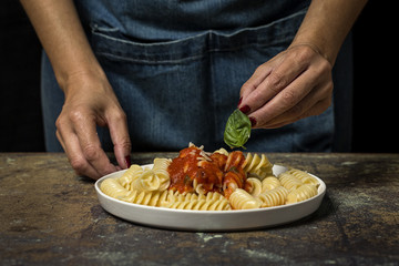 Person decorating pasta with basil