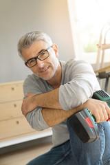 Portrait of cheerful man doing DIY home improvement