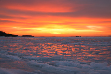 The sea is covered with ice at sunset.