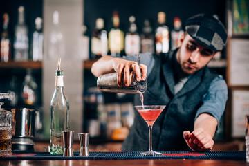 Barman pouring fresh cosmopolitan drink