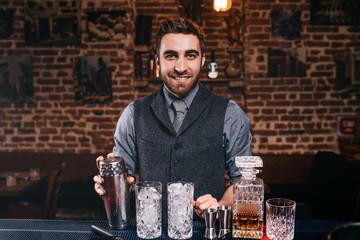 Barman smiling at camera while preparing drinks at bar. Alcoholic drinks and professional bartender
