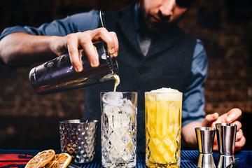 Elegant bartender pouring fresh orange vodka cocktail over ice in crystal glassware