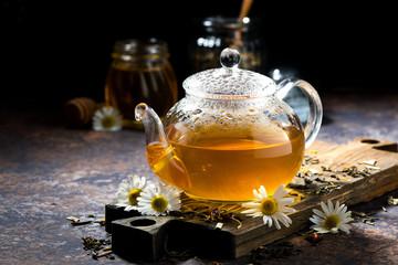 glass teapot of fragrant chamomile tea on dark background