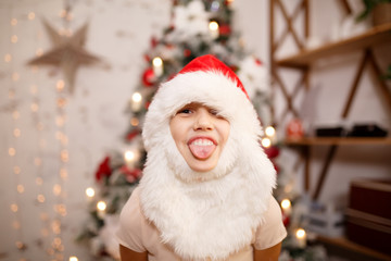 Photo of girl in Santa hat with beard showing tongue against background of New Year's decorations
