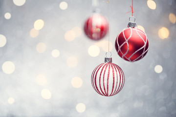 Image of three Christmas red balls on gray background with spots.
