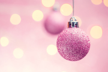 Picture of two New Year's pink balls on pink background with spots.