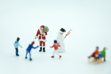 Christmas, Kid and family Concept. Santa Claus and children miniature figure with snowman walking and playing on white background.