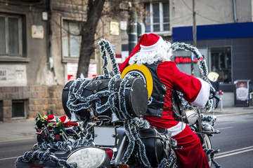 a man dressed in a Santa costume drives a motorcycle and hasten to leave presents to obedient children. Santa Claus as a rocker.a lightly blown-up rocker with red clothes and a hat instead of a helmet