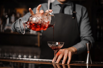Barman in a tie and apron pouring red alcoholic drink in a cocktail glass
