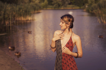 Brunette sexy cute woman in ethnic style bohemian boho hippie dress and jewelry in the park. Slim fit body. Sunny day, summer evening. Copy space