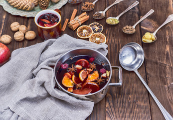 mulled wine in a saucepan and iron spoons with ingredients