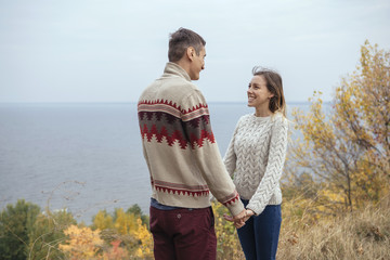 Happy thoughtful couple standing on a cliff near sea hugging each other in cold foggy cloudy autumn weather. Copy space
