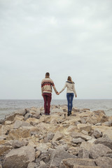 Happy thoughtful couple standing on a rock beach near sea hugging each other in cold foggy cloudy autumn weather. Copy space