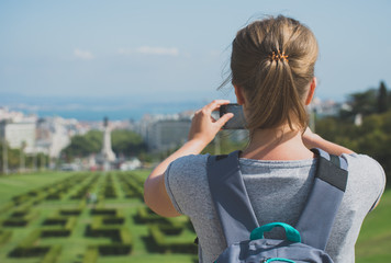 Woman tourist with smartphone in Eduardo VII Park in Lisbon.