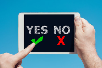 """Man holding a tablet device with """"yes no"""" icons as decision concept"""