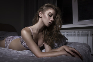 Cute gorgeous sexy young woman alone laying in bed at home in seductive lingerie. Fit slim body, fashion glamour portrait, clean fresh skin. Dark dim dramatic light. Copy space