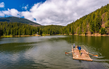 Synevyr, Ukraine - May 09, 2017: wooden raft with tourists on Synevyr lake. Beautiful springtime nature scenery in the most visited location of Carpathian mountains