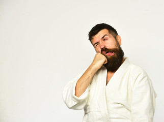Karate man with suffering face in uniform. Japanese martial arts