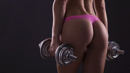 Close up of a beautiful caucasian young woman fit athletic body in sportswear pumping up rear butt bottom muscles with heavy dumbbells. Sexy curves. Neutral dark background