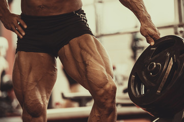 Close-up of bodybuilders muscular legs. Athlete man doing workout exercise in gym.