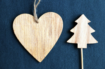 Christmas decoration with wooden heart and fir tree figurine on blue felt background. Winter holidays,Merry Christmas,Happy New Year concept.