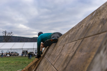 Athlete climbing over a wooden wall at an obstacle course race