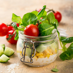 Homemade salad in glass jar with corn salad and vegetables. Healthy food, diet, detox, clean eating and vegetarian concept.