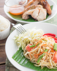 Green papaya salad,Som tum Thai and grilled chicken on wood table