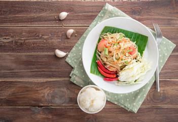 Green papaya salad,Som tum Thai on wood table,top view
