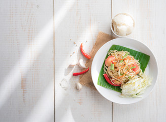 Green papaya salad,Som tum Thai on wood table,top view