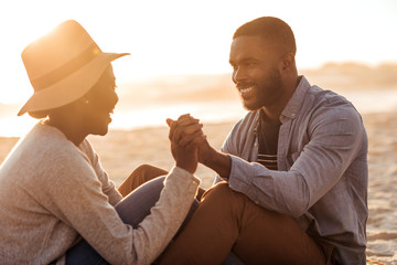 Young African couple sitting together on a beach at sunset