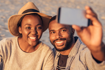 Content young African couple taking selfies together at the beach