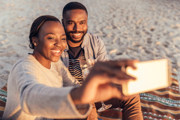 Smiling African couple sitting together at the beach taking selfies